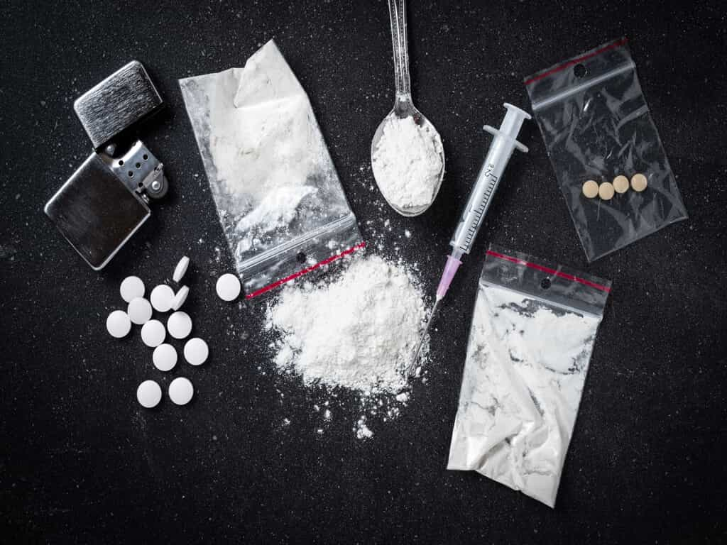 Black Table with White Power in a Bag, Pills in a Bag, a Spoon with White Powder, Syringe, & Lighter
